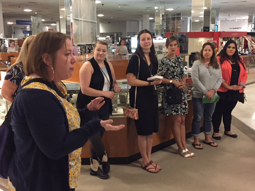 Runaway and Homeless Youth Program Director, Kirstin London, talks with Macy's staff members about Looking Glass during the kickoff of the Big Give Back fundraising initiative.