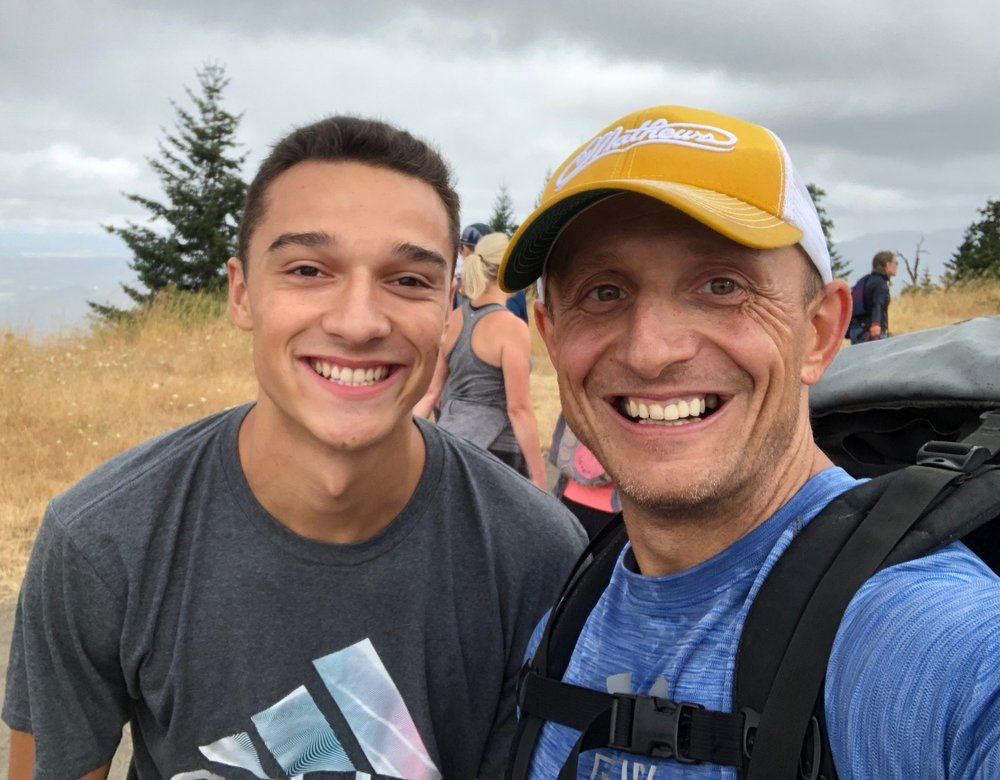 "Nick ""the trainer dude"" Hammond (right), poses with fellow Looking Glass supporter Pierce LaCoste, at the summit of Mount Pisgah. Nick wore a backpack weighing about 35 pounds to add to his personal challenge hiking the mountain trail - and he also ran for most of it."