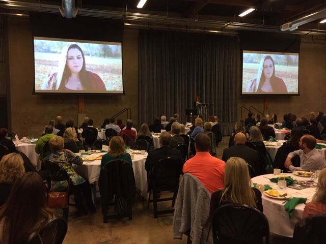 Looking Glass event attendees enjoy breakfast while they watch a success story video from a former Looking Glass client at Venue 252.