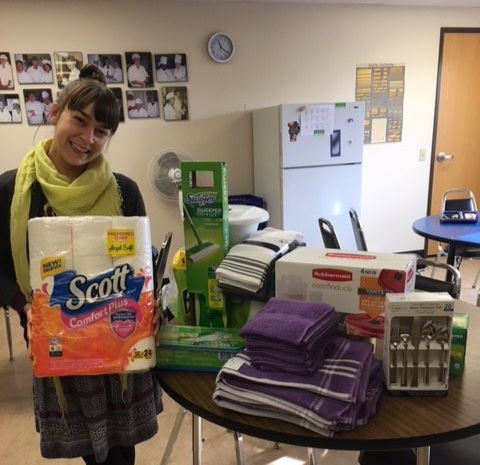 Riverfront Admissions Counselor, Shannon Grosse, displays a variety of items purchased for Looking Glass youth clients using funds donated by SELCO Community Credit Union.