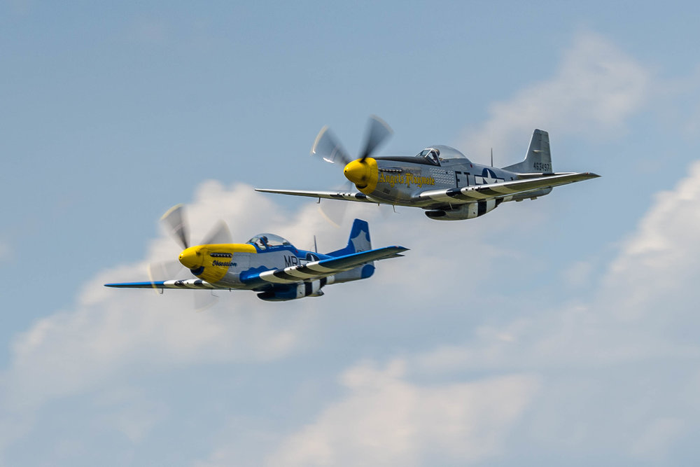 "A Mustang formation fly-by in tribute to Lt Goebel Dr Alex Newsome in P-51D ""Angel's Playmate"" and Jeff Micheal in P-51D ""Obsession"""