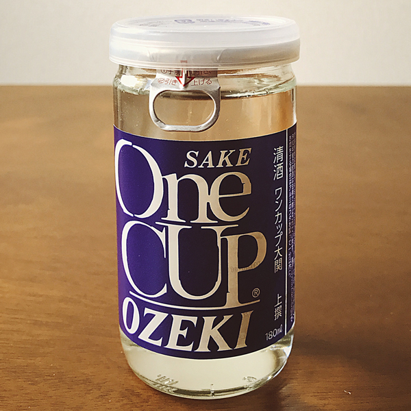 "大関 ワン カップ 上撰 - Ozeki One Cup Superstar - ¥ 216 Superstar?! Why yes, yes I am. Or maybe 上撰 (up, selection) should be translated as ""superior"". Anyhow, I love this stuff. I cook with it. I chill with it. I wonder how it is perceived by locals. (A nice standard? Or cheap swill, a la natty lite?)"