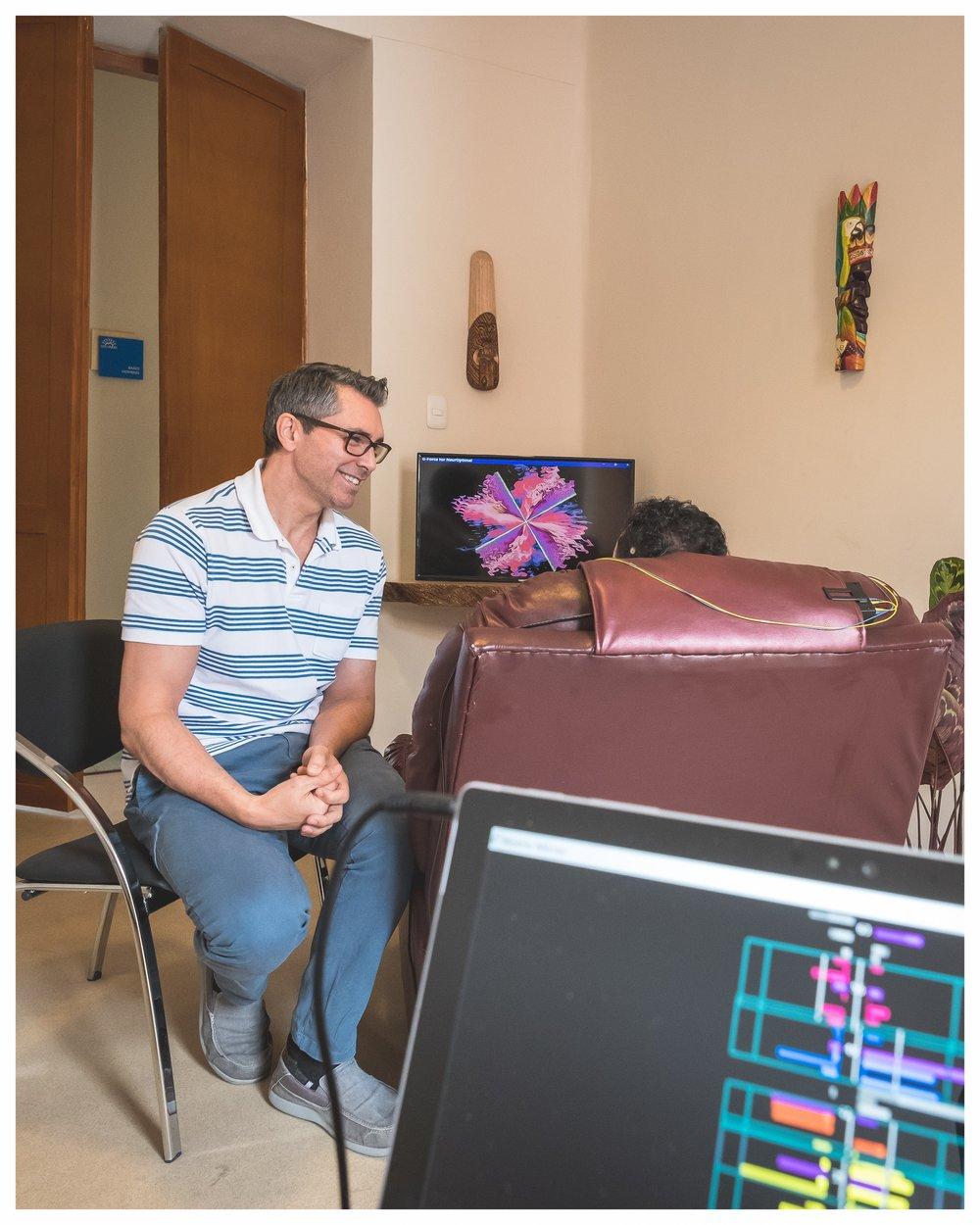 ¿Cómo trabaja Neurofeedback? - Neurofeedback es una forma avanzada de biorretroalimentación que detecta información sobre la actividad de las ondas cerebrales.La electricidad generada por el procesamiento del Sistema Nervioso Central (SNC) es detectada por sensores y visualizada por el especialista en un monitor en tiempo real, esto se llama electroencefalografía o EEG.Durante la sesión de Neurofeedback, el usuario recibe una estimulación visual y auditiva que le permite entrar en un estado de relajación. El sistema detecta en tiempo real los cambios bruscos en la actividad cerebral e inmediatamente informa al cerebro con una interrupción audible en la música; esta interrupción invita al cerebro a volver su atención al momento presente, lo cual le permite mejorar su capacidad de procesamiento de información, resiliencia cerebral y eficiencia.Este comportamiento cerebral se convierte en un hábito que transforma al cerebro,lo cual mejora de manera sostenible la salud mental de la persona.(Fotografía de una sesión de Neurofeedback en Sol de los Andes)