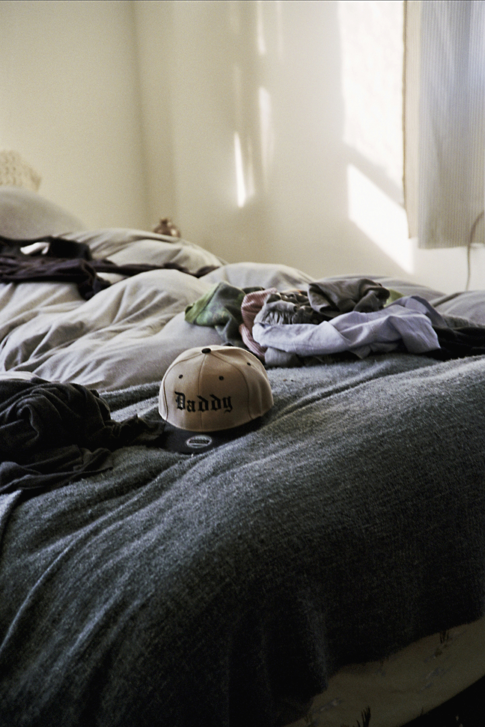 A baseball cap from a Tom of Finland Foundation dinner sits on the bed. Opposite: Ernst reclines at home.