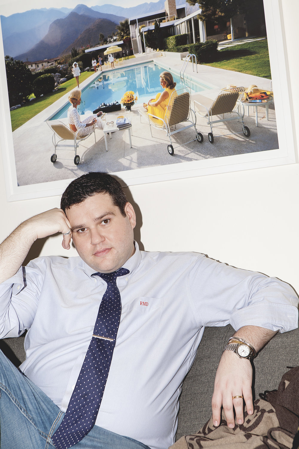 Blogger Ryan Dziadul reclines beneath a Slim Aarons print.