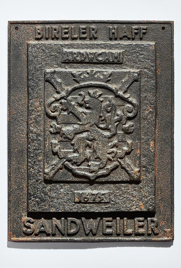 Reproduction de la plaque en fonte du Birelerhof éditée par les Sapeurs pompiers de Sandweiler / Reproduktion der Ofenplatte vom Birelerhof, herausgegeben von der Feuerwehr Sandweiler,  15,5x20,5cm