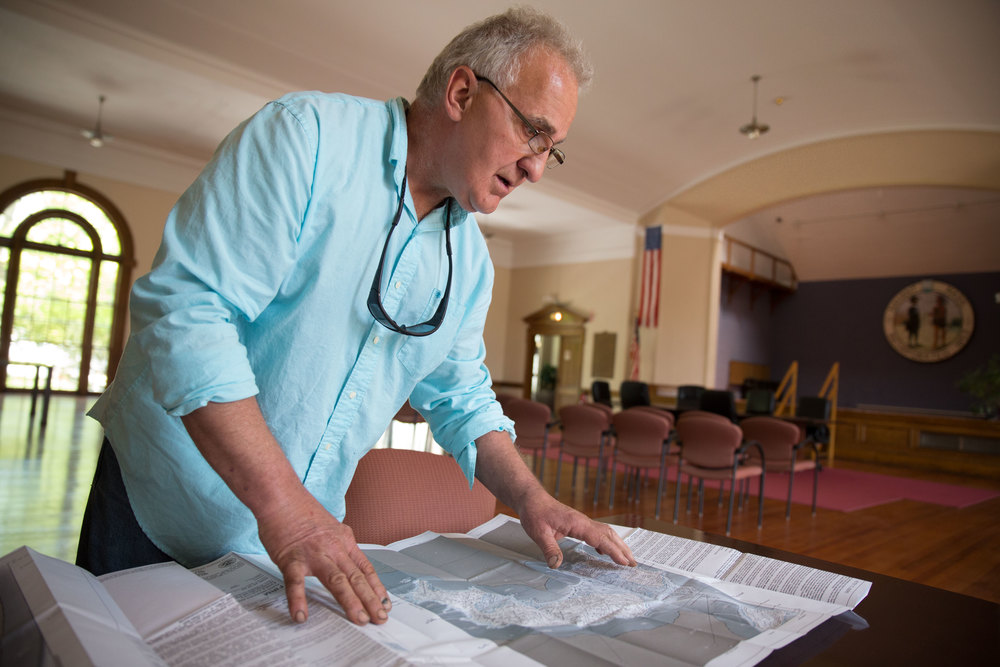 Enzo Barile, a local elected official who has taken on heading up the town's preparedness measures, pours over federal flood-risk maps for Nahant.