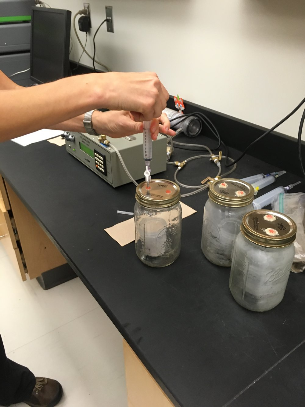 A syringe is used to extract CO2 from the mason jar.  Photo: Logan Shannon