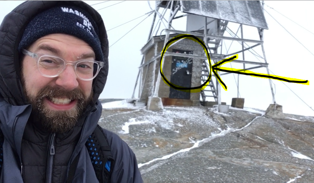 """Selfie courtesy of Taylor Quimby. Directly behind the """"Kind is Cool"""" boulder is the Mt. Cardigan fire tower, complete with graffiti."""