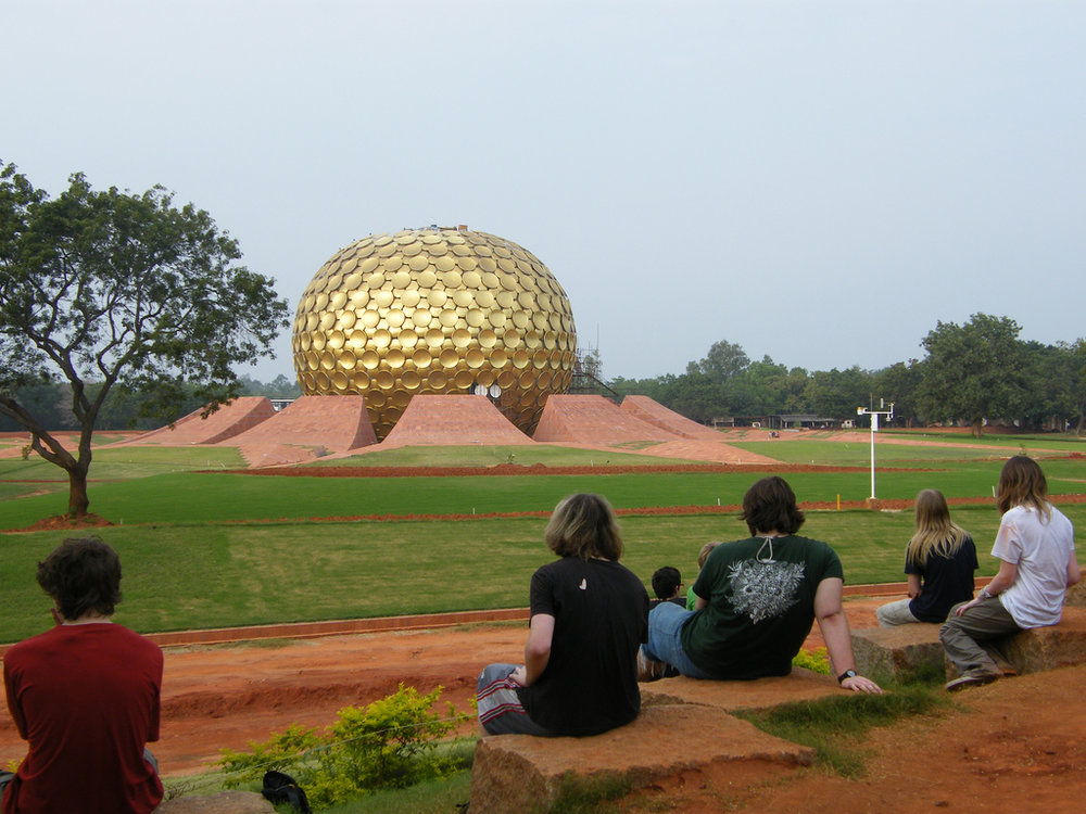 "Auroville (City of Dawn) is an experimental township in Viluppuram district mostly in the state of Tamil Nadu, India with some parts in the Union Territory of Puducherry in South India. It was founded in 1968 by Mirra Alfassa (known as ""the Mother"") and designed by architect Roger Anger. As stated in Alfassa's first public message in 1965, she states, that Auroville is meant to be a universal town where men and women of all countries are able to live in peace and progressive harmony, above all creeds, all politics and all nationalities. The purpose of Auroville is to realise human unity."