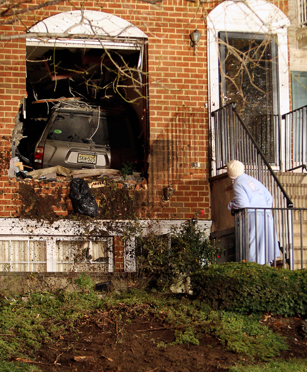 A neighbor takes a peek at a Nissan Pathfinder which crashed and landed in the house belonging to Gloria Sinclair, 74, Friday night December 8, 2011, near the intersection of West Market Street and Wickliffe Street in Newark. No one was injured.  (Photo Credit: Saed Hindash)