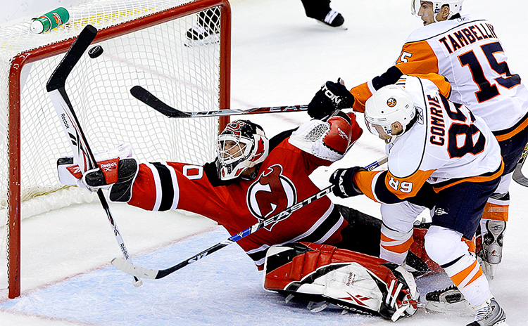 New Jersey Devils' Martin Brodeur makes an amazing diving save with only 12 seconds left in the game under pressure from Mike Comrie and Jeff Tambellini of the New York Islanders. Devils won 2-1.  (Photo Credit: Saed Hindash)