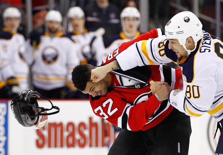 Buffalo Sabres right wing Chris Stewart (80) lands a punch to the head of New Jersey Devils defenseman Mark Fraser taking off his helmet during their fight in the first period at the Prudential Center.  Newark, NJ.  1/6/15  (Photo Credit: Saed Hindash)
