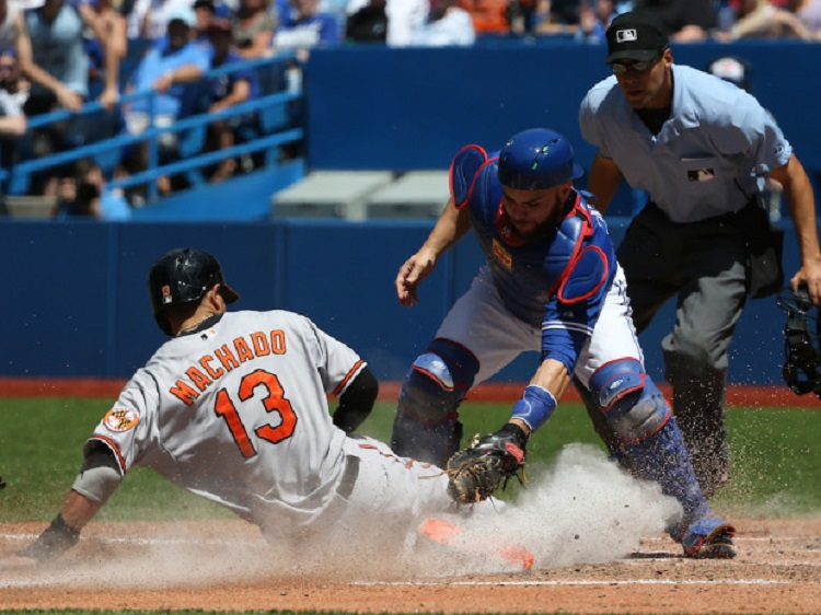 Orioles' Manny Machado slides safely into home plate to score a run in the sixth inning. Photo: Tom Szczerbowski/Getty Images.