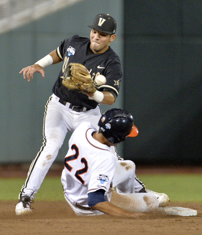 Virginia Cavs SS Daniel Pinero (22) slides into second base against the Vanderbilt Commodores. The Cavs edged Vandy 4-2 to win the College World Series in Omaha.