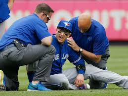 Blye Jays trainers Mike Frostad and George Poulis tend to injured SS Troy Tulowitzki Saturday afternoon at Yankee Stadium.