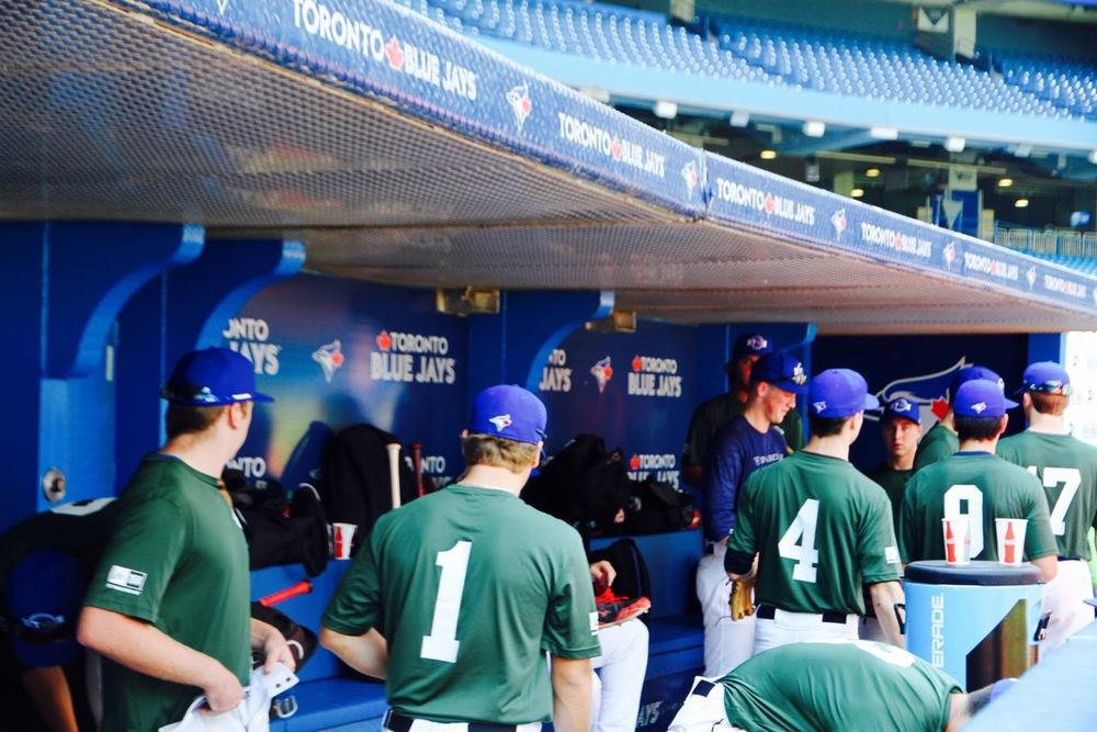 Ontario Green congregates in the dugout. (Tyler King/Canadian Baseball Network)