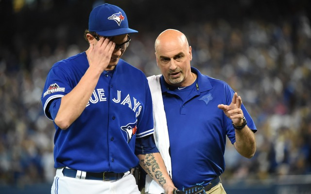 RP Brett Cecil is walked off the field by Blue Jays trainer George Poulas after tearing his calf in the eighth inning.