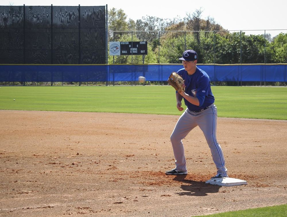 Christian Williams takes fielding practice at first base. Photo: Kyle Forster