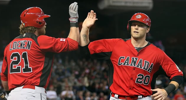 Michael Saunders, right, is greeted by Adam Loewen after a home run in 2013.