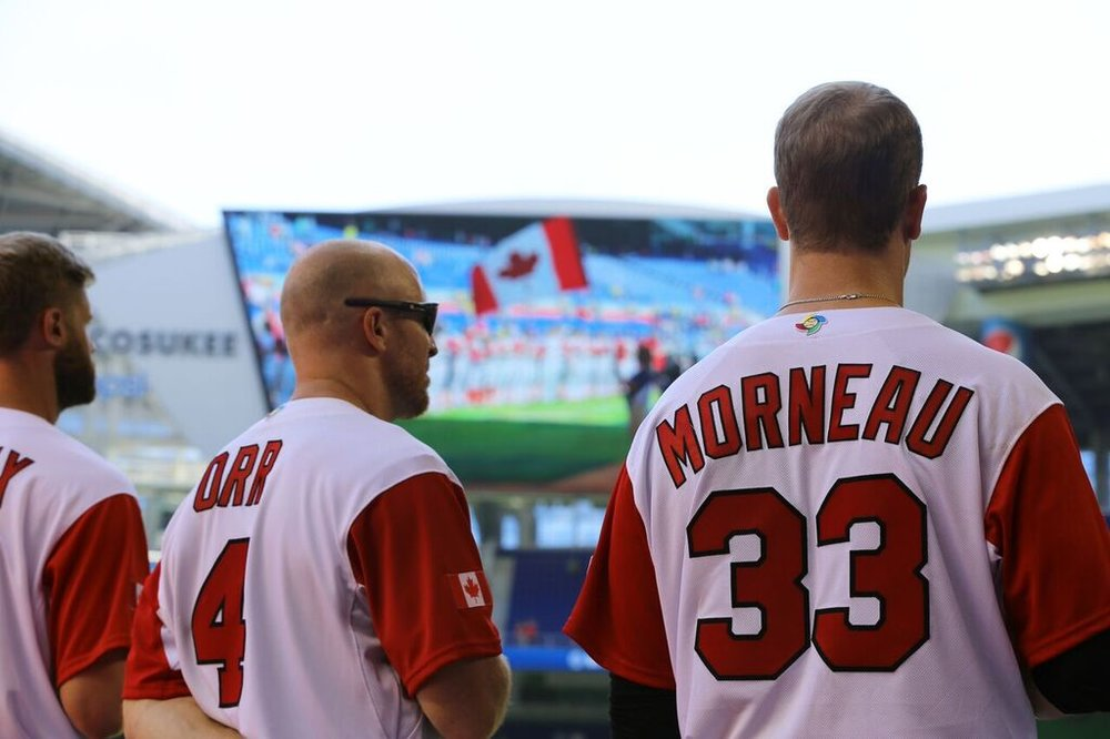 Peter Orr (4) and Justin Morneau (33) at attention during the anthems.