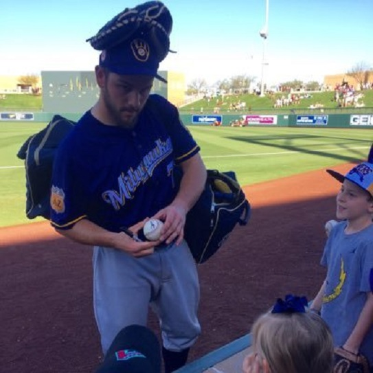 C Dustin Houle (Penticton, BC), former Langley Blaze who made an impression at the Milwaukee Brewers major-league camp, autographs a ball for a young fan this spring.