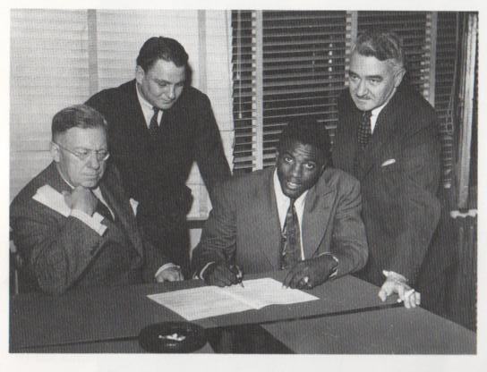 In 1945, Royals president Hector Racine (seated) invites Jackie Robinson to sign a Royals contract. Also in the photograph are Branch Rickey, Jr., (standing) and Royals vice president Romeo Gauvreau. (far left) Photo: Daniel Papillon