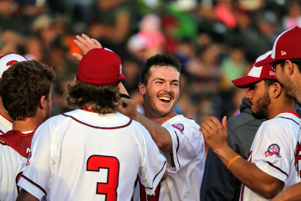 Okotoks Dawgs infielder Greg Cullen (centre) celebrates with this teammates during his club's 4-1 win on Sunday. Photo Credit: Amanda Fewer