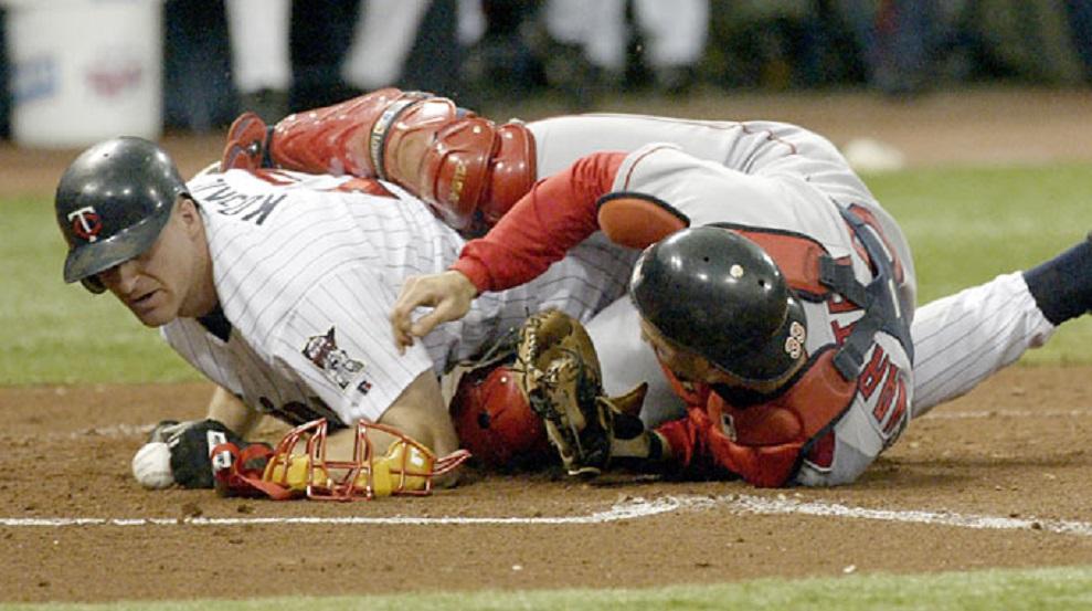 Twins 3B Corey Koskie (Anola, Man.) cracks Boston Red Sox C Jason Varitek to knock the ball loose.