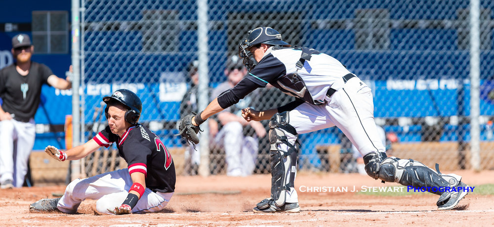 Victoria Eagles base runner Chad Heglend slides pass the tag of White Rock catcher Sam McPherson during game one action Friday (Photo: Christian J. Stewart / ISN)