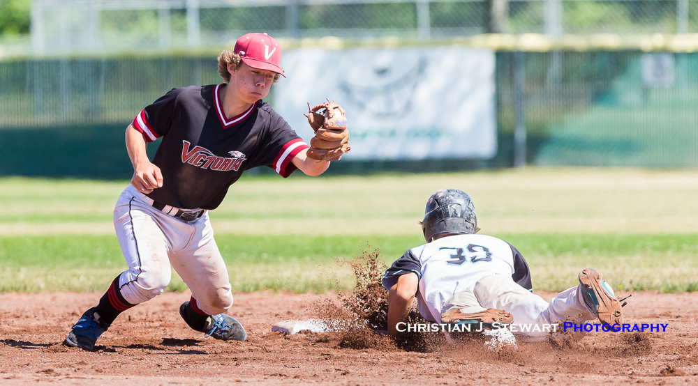 White Rock's Rhys Folick slides safely into second base as Victoria Eagle's shortstop Brad Cox is a bit late with the catch and tag in opening game action Friday morning (Photo: Christian J. Stewart / ISN)
