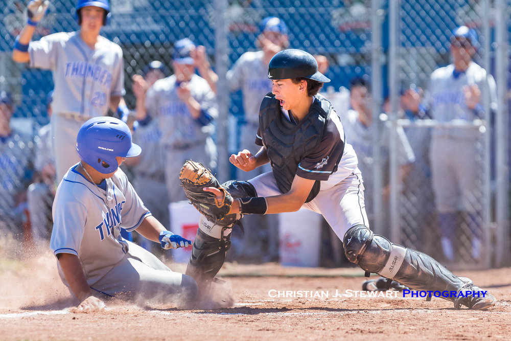 In game two action Friday, UBC Thunder player Matthew Suarez slides safely into home under the tag of White Rock catcher Holden Comiskey (Photo: Christian J. Stewart / ISN)