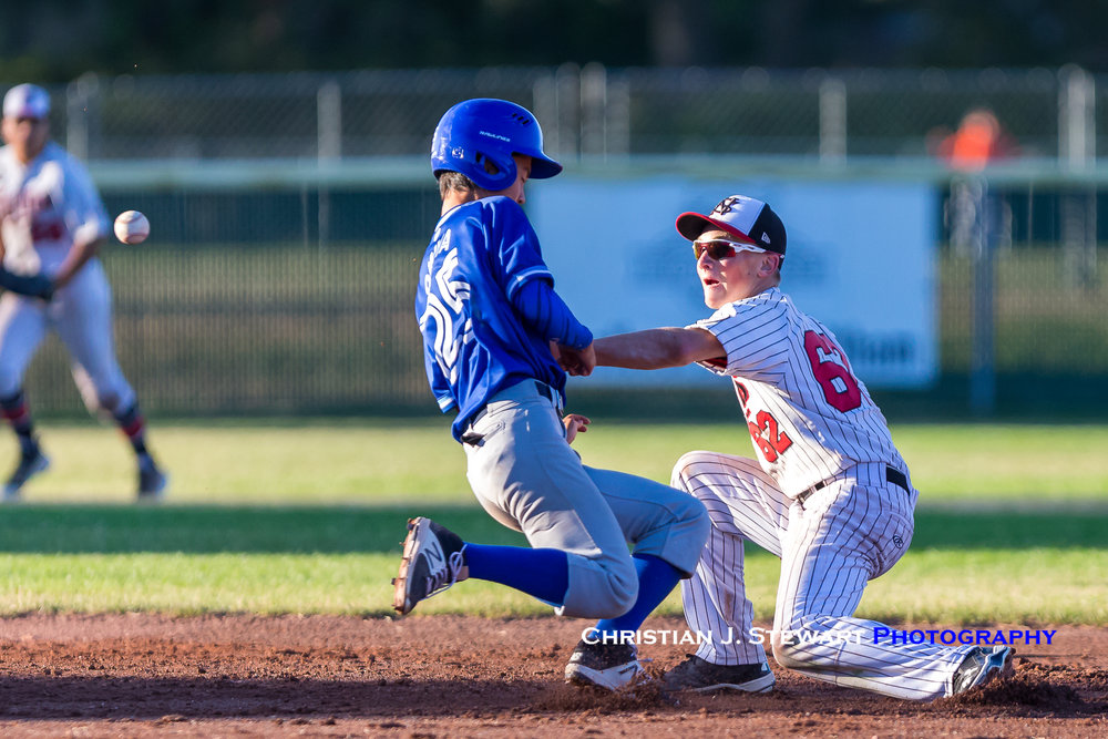 North Delta's Yugo Omiya (left) scrambles back to second base on a pick-off attempt as North Shore shortstop Matt Wiseman waits for the throw (Photo: Christian J. Stewart / ISN)