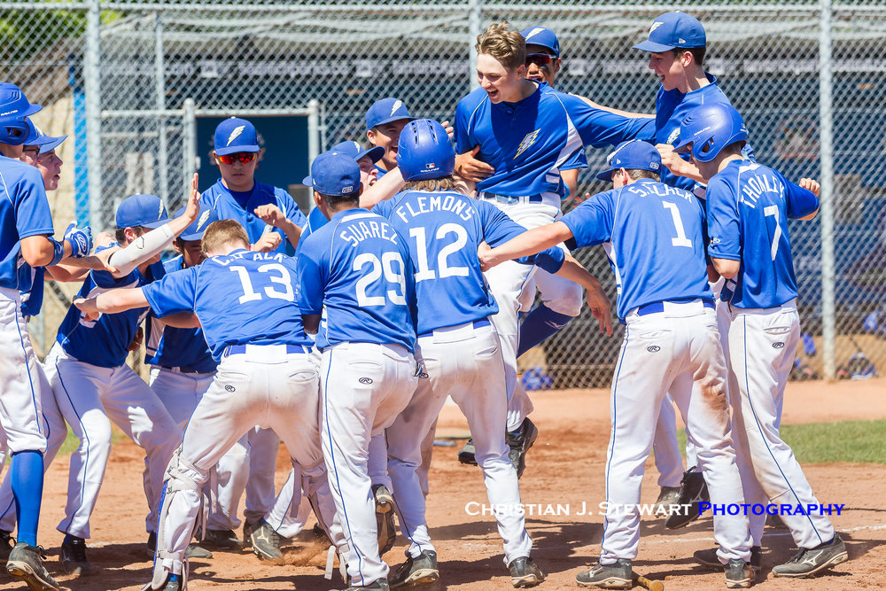 UBC Thunder's Eli Saul (centre no helmet) jumps on to home plate among his awaiting teammates after hitting a two-run home run to win Sunday morning's qualifier game against North Delta (Photo: Christian J. Stewart / ISN)