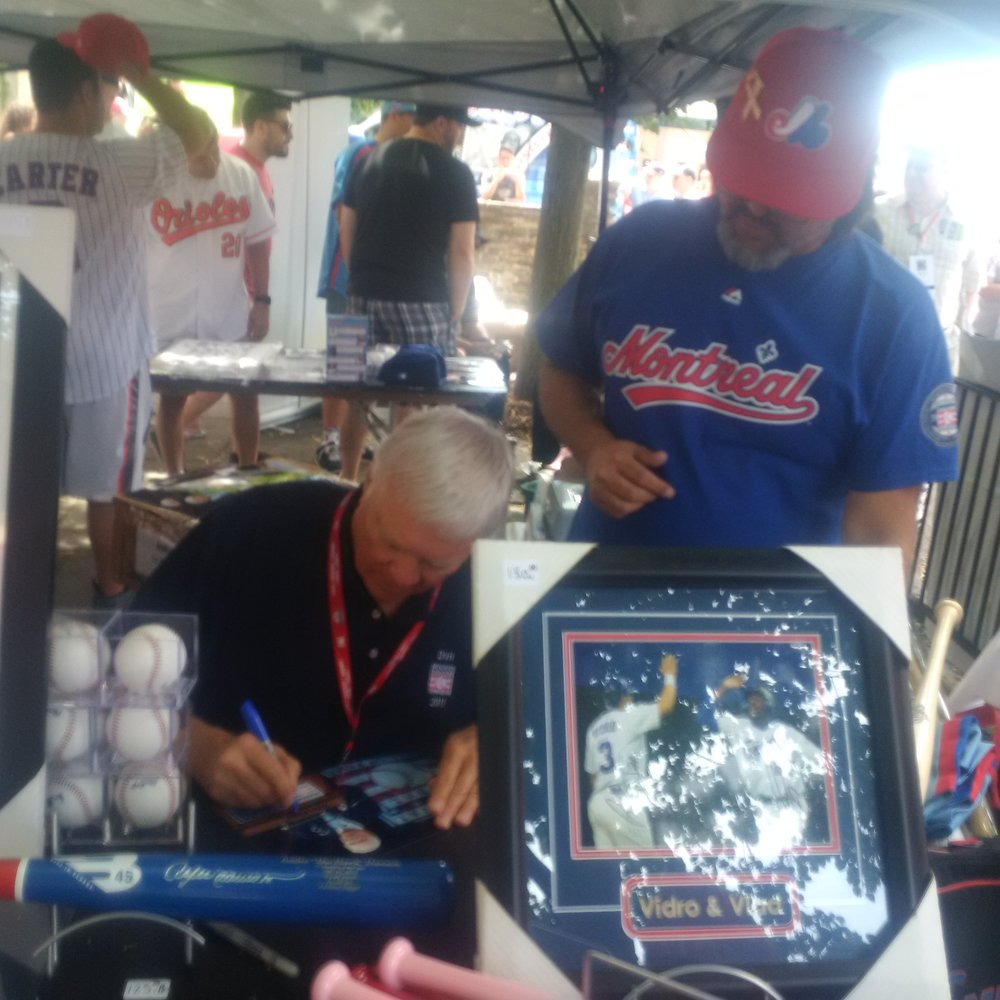 Canadian Baseball Hall of Famer and former Montreal Expos broadcaster Dave Van Horne (left) signs an autograph on Saturday in Cooperstown, while ExposFest organizer Perry Giannias (right) looks on.