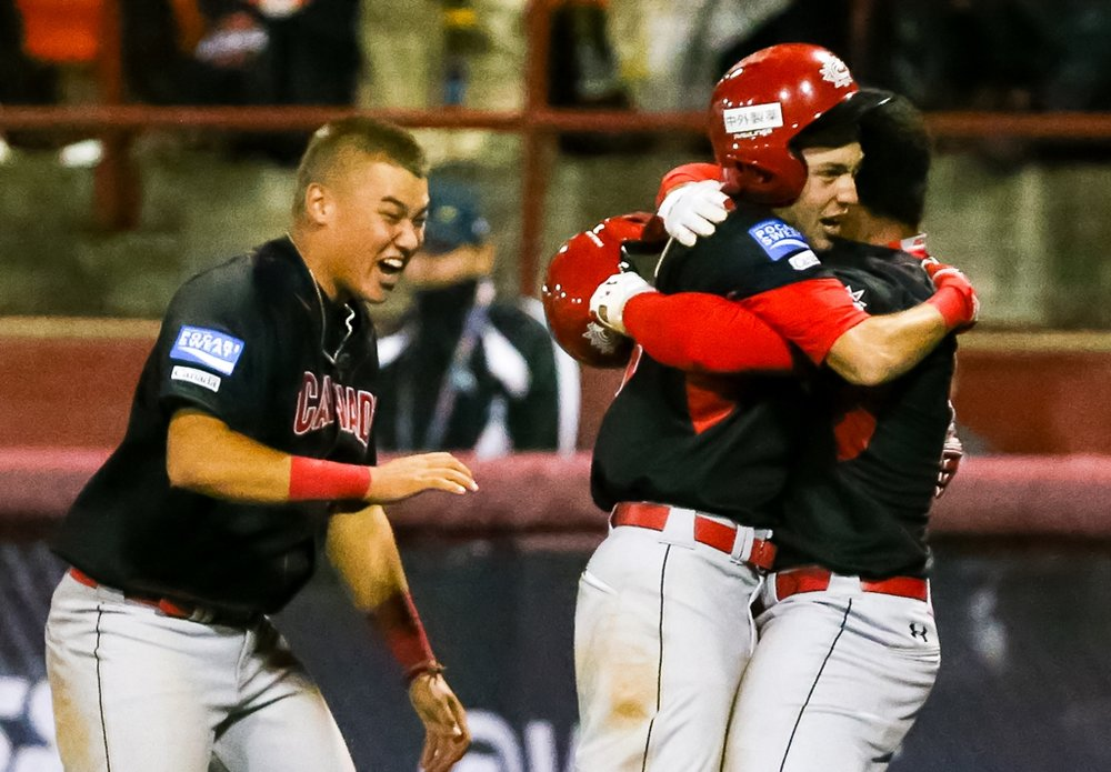 Canadian Junior National team members celebrate after scoring the winning run against Italy at the U18 Baseball World Cup in Thunder Bay, Ont., on Monday. Photo Credit: WBSC/Christian Stewart