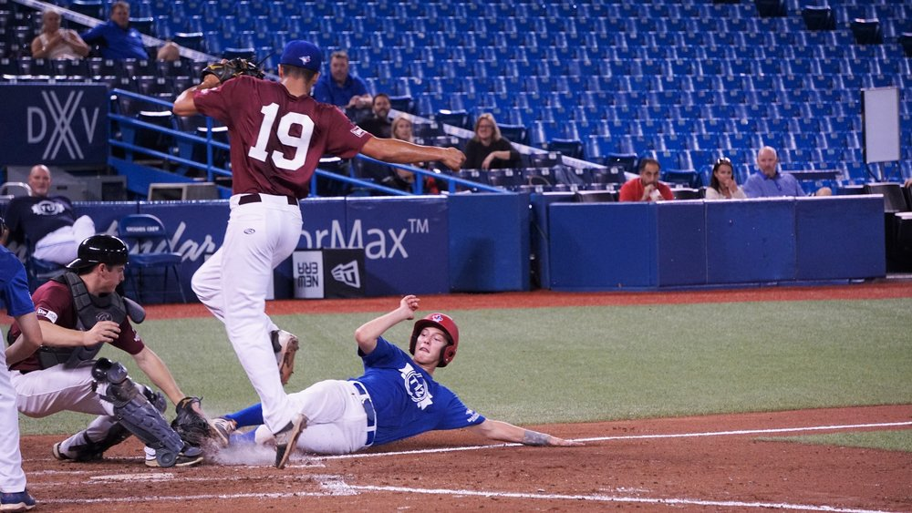 Quebec catcher Philippe Breton attempts to score but is unable to beat the tag. Quebec did, however, go on to beat the Atlantic squad 4-1 at Tournament 12 at Rogers Centre on Saturday morning. Photo Credit: David Morassutti