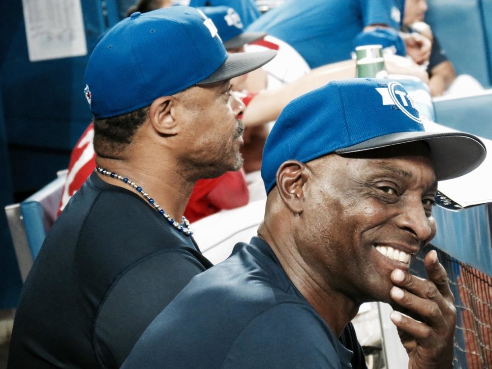 Jesse Barfield annd Lloyd Moseby share a memory in the 1B dugout.