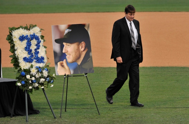 Roy Halladay, Jr. walks by a picture and wreath of his late son after speaking at Spectrum Field in Clearwater on Tuesday.