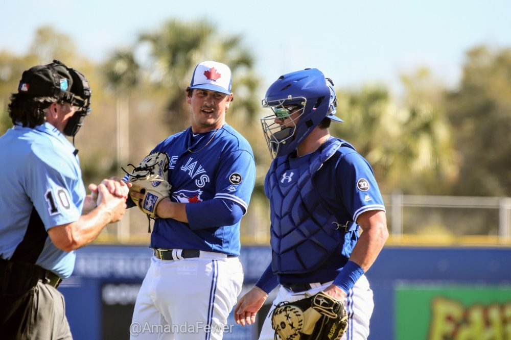 Case (middle) converses with Blue Jays catcher Reese McGuire, while home plate umpire Phil Cuzzi gets ready to hand Case the ball on Sunday.