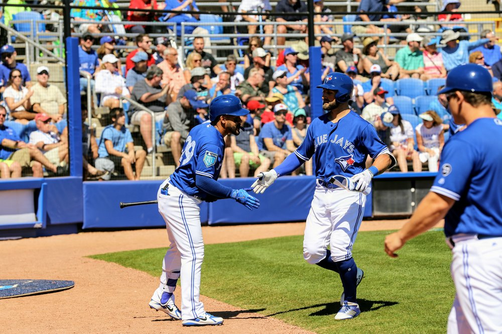 Blue Jays centre fielder Kevin Pillar (centre) is congratulated by second baseman Devon Travis (left) after belting a two-run home run in the second inning.