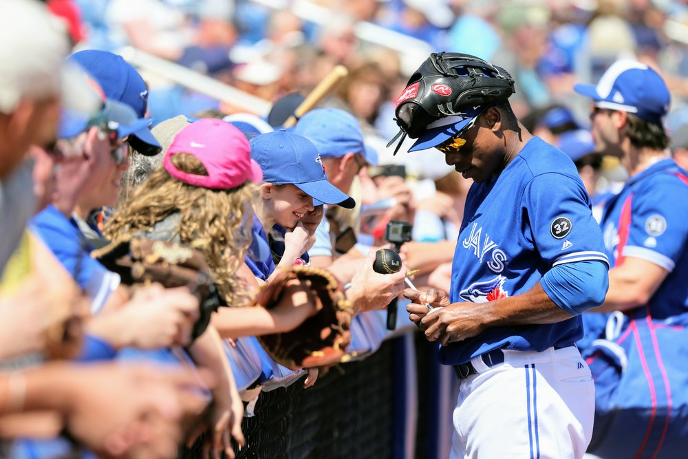 Outfielder Curtis Granderson, who belted his third home run of the spring in Wednesday's game against the Pirates, signs autographs for fans at Dunedin Stadium.