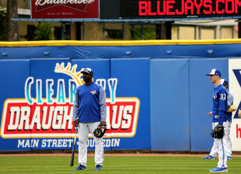 Gold Glove winner Devon White in the  outfield during batting practice with a familiar name:  RHP Braden Halladay.