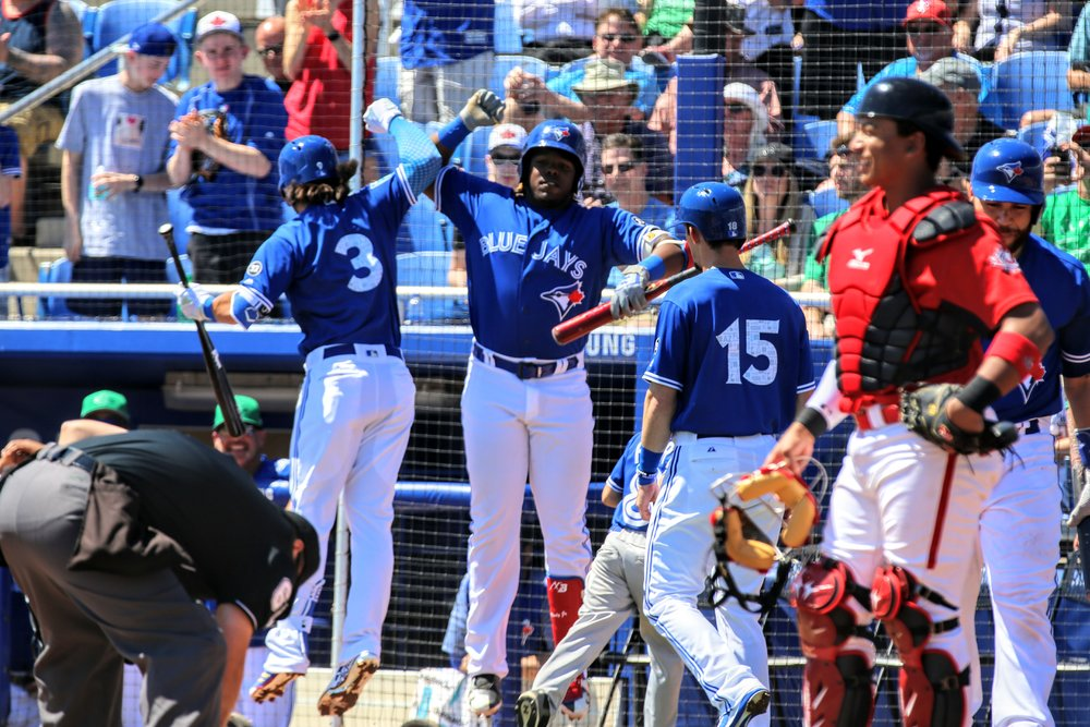 Bo Bichette (left) and Vladimir Guerrero Jr. (centre) celebrate after Bichette's two-run home run in the first inning.