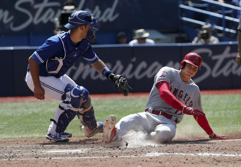 DH Ohtani slide in safely ahead of the tag of Blue Jays catcher Luke Maille.