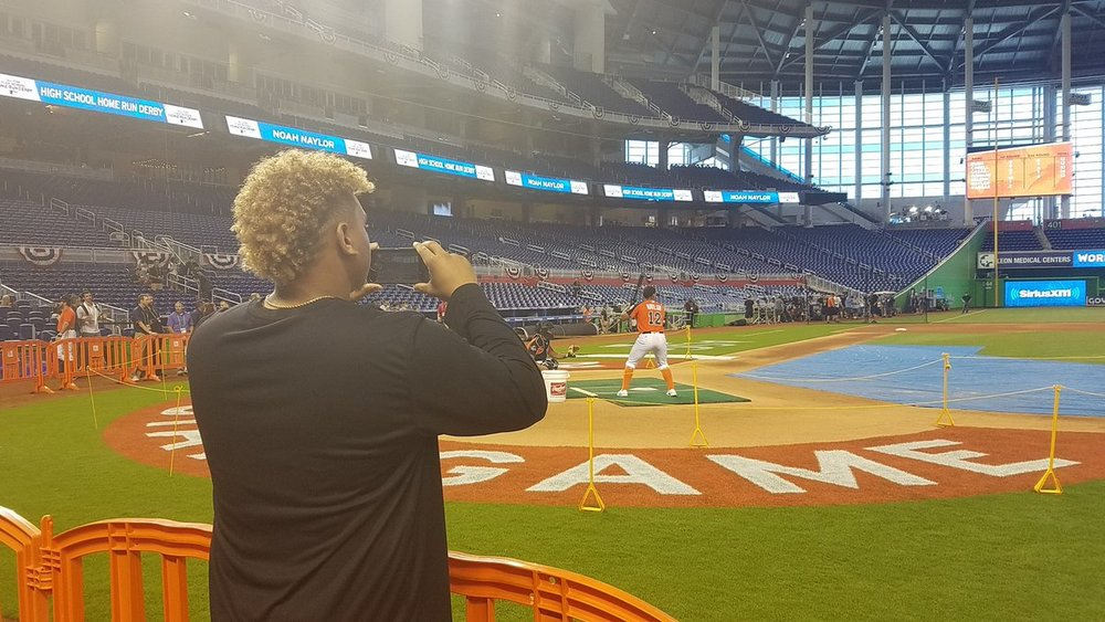 Josh Naylor stands behind the temporary fence to take a picture of his brother Noah Naylor competing in last year's Junior Home Run Derby at Marlins Park in Miami. Photo: JJ Cooper, Baseball America.