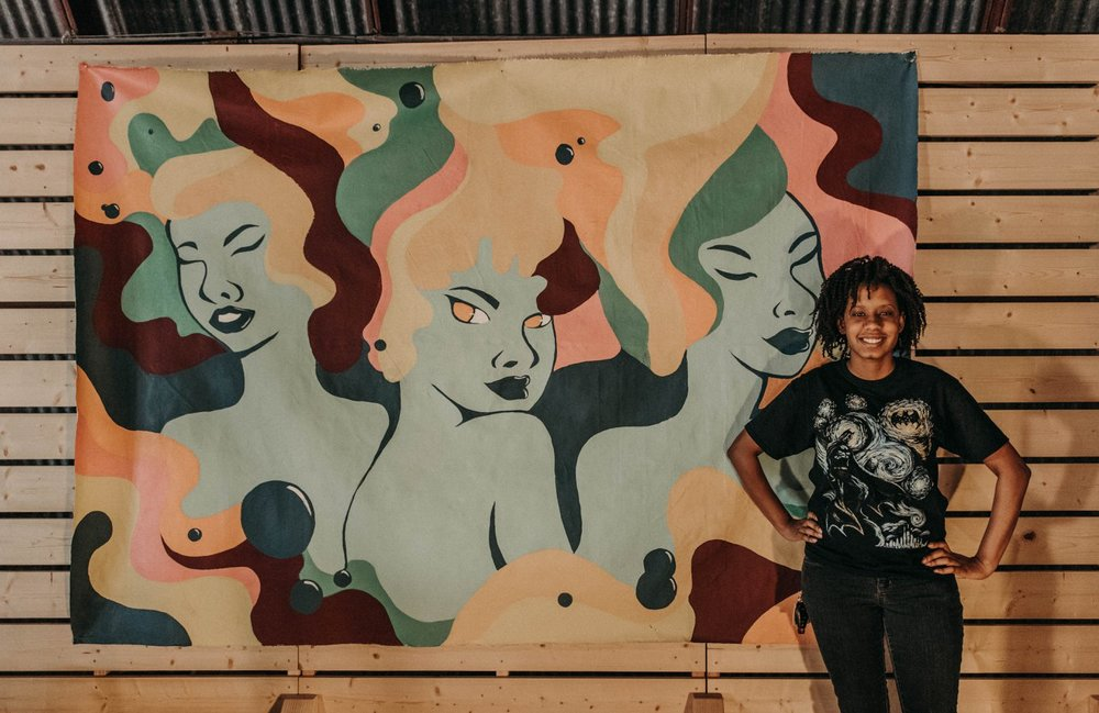 Kwanzaa Edwards in front of the craftHER Market Spring '18 community mural. Photo by 1778 Photographie