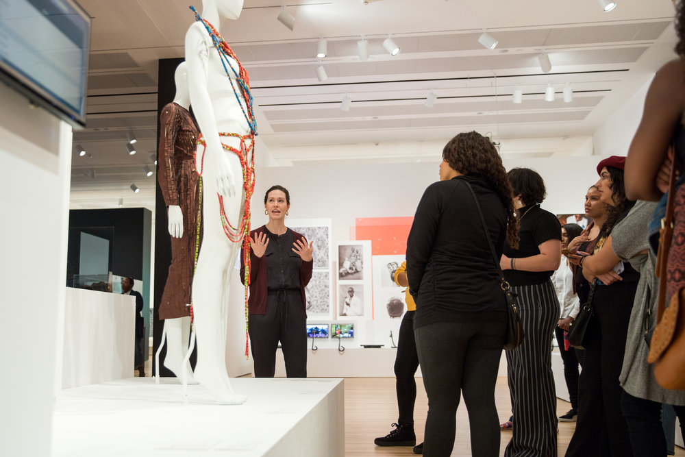 Associate Curator Claire Howard and visitors discuss Fabrice Monteiro and MISWudé, Waxology, No. 1, 2014. Photo by  Whitney Devin.