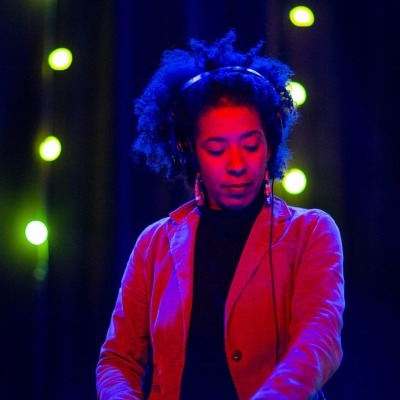 """DJ Shani  Heavily influenced by the soul, funk & jazz scenes of Chicago's south side, DJ Shani has always been enveloped by music. Throughout her childhood, her family taught her the roots of her sound (Zydeco, Blues, Jazz, Reggae, Funk, Soul), while the radio (Energy 88.7fm, B96, WGCI) taught her the future of her sound. After a few years in the rave scene, first as a patron then as a promoter, she noticed that the energy was inviting, but it was  missing  something. While she was a junior at Loyola University - Chicago, she set in motion what would be her biggest contribution to the House music scene to date.  In May of 1998, DJ Shani created & produced a  Deep House  radio show coined """"The Groove Temple®"""" on WLUW-88.7FM that filled a void for the most prominent, yet canceled house music radio station, WBMX. She has a humble, personal & realistic outlook about the DJ craft, """"For me, it was & still is about sharing music, providing a music experience to people & giving exposure to DJs who aren't given the chance to play out. I come from musicians – both grandfathers played music in the same band. My grandmother played piano, my uncle plays guitar and my immediate family still plays music for a living.""""  Her father, was an avid record collector, her stepfather, guitarist Abdul Hakeem of the world music Chicago-based group Funkadesi, toured with Rita Marley when she was in high school. Her brother, who goes by the moniker KrushLove, has been making music longer than she's been a DJ. Her mother is the only one that doesn't make music, but she more than makes up for it by being a playwright. When people say they've grown up with music, she relates.  Even after her graduation from Loyola in 2001, she continued to produce The Groove Temple®, was a freelance writer for various Chicago music magazines (5Magazine, L'Afrique) & worked at the famous Gramaphone Records. There, she helped promote both, by organizing the first ever record fair between Gramaphone & WLUW. In 2004 """