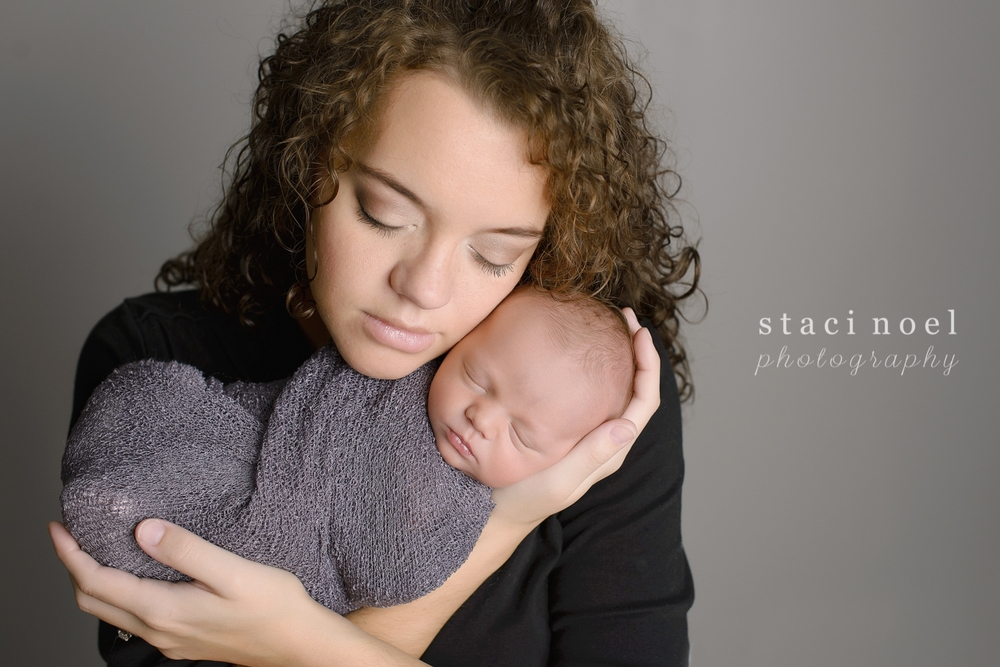 Newborn baby boy in Concord, NC photographed by Staci Noel photography with his mother on grey backdrop.